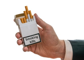 Man holds cigarette pack in hand with warning label that smoking kills. Isolated on white background.
