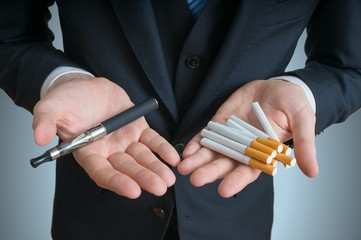 Man is holding vaporizer and conventional tobacco cigarettes and comparing or offering.