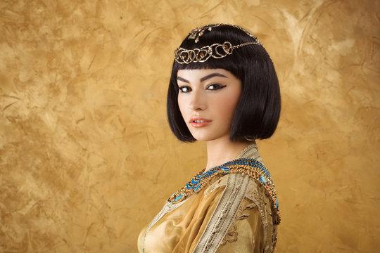 Beautiful Egyptian woman like Cleopatra on golden background