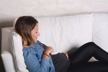 Young pregnant woman holding baby booties on her abdomen.