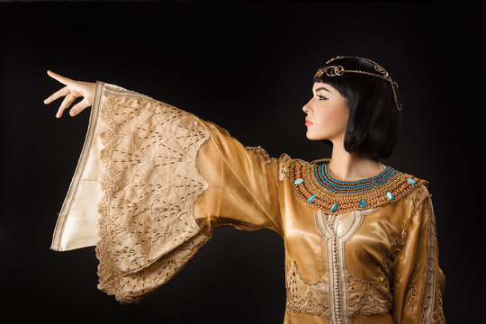 Beautiful Egyptian woman like Cleopatra pointing finger away on black background