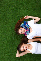Two pretty girls lying on the fresh green grass