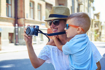 Close-up of smiling woman with small son talking photo during wa