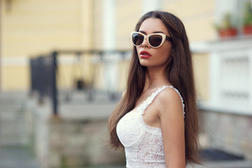 Outdoor summer portrait of young beautiful trendy girl in white dress and sunglasses.