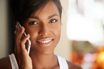 Cropped portrait of cute African American brunette businesswoman with short hairstyle looking at the camera with thoughtful smile, calling her partner, making an appointment, listening attentively