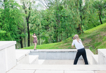 photographer takes a woman standing on the stairs in the park