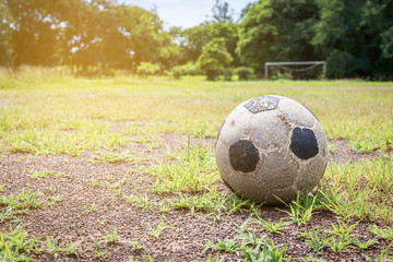 Old football on the field and small gravel