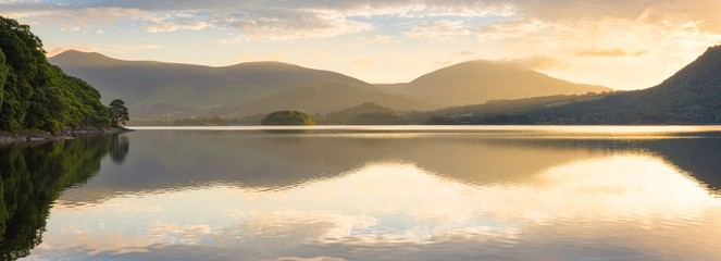 Golden sunlight shining through mountains on peaceful calm morning at Derwentwater, Lake District, UK. Wall mural