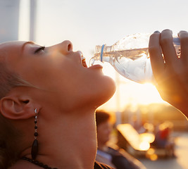 Portrait of beautiful young woman drinking water outdoors