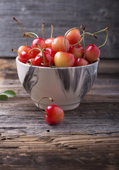 Ripe yellow cherries in wooden bowls