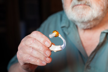 man holding hearing aid