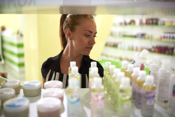 Young woman consultant lays out beauty on store shelves