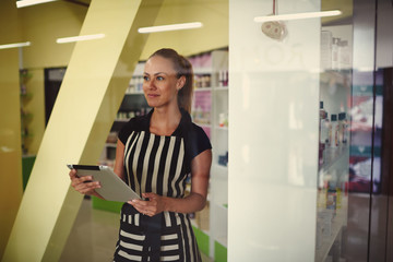 Young attractive saleswoman using digital tablet while standing in pharmacy