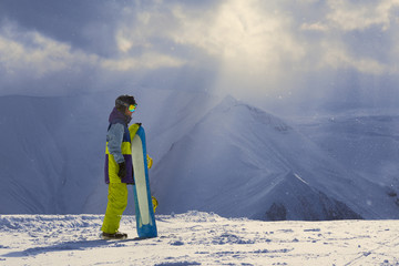 Snowy weather in the mountains snowboarder stands sideways