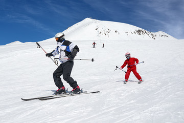 Ski instructor teaches to ride. The child repeats teacher.