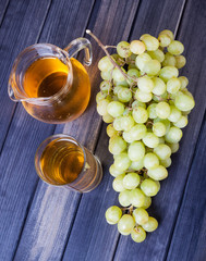 green grape bunch and a pitcher of  juice top view