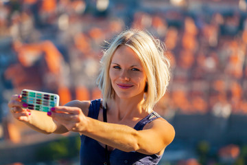 Female traveller make a selfy photo against the background of the old city of Dubrovnik from the mountain to her phone for Instagram or other social networks. Travel to Croatia. Summer vacation.
