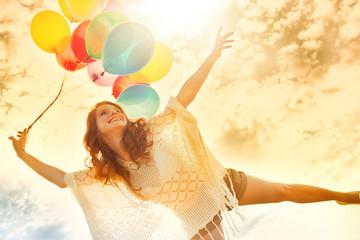 Frau mit Luftballons im Sonnenuntergang