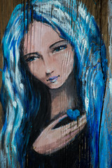 Portrait of woman with blue hair holding small heart in hand, painted on a wood with acrylics.