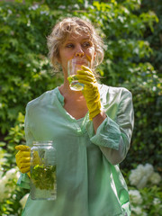 Attractive woman during a pause drinking water with mint and lem