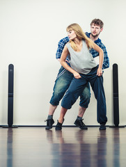 couple of young man and woman dancing hip-hop