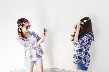 Two young girls are standing in front of the white wall and takeing a pictures of each other.
