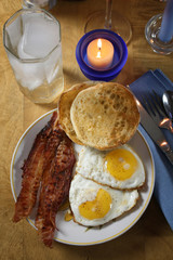 Bacon, eggs, english muffin via candle light suggest breakfast for dinner