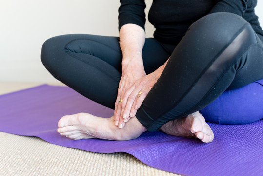 Close up of older woman's hands and feet, sitting cross legged on purple yoga mat and cushion (selective focus)
