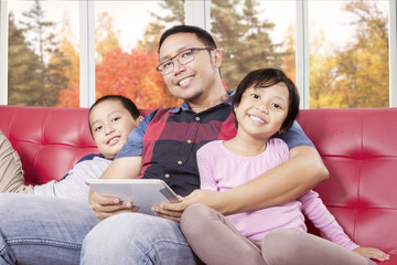 Two kids and their father with tablet sitting on sofa