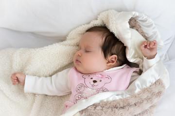 Newborn baby sleeps on the bed in woolen clothes