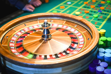 Roulette in motion. Green table with colored chips ready to play.