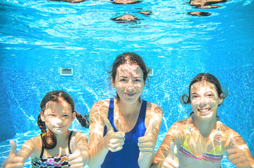 Family swims in pool underwater, happy active mother and children have fun, kids sport on vacation