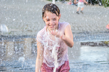 Happy girl having fun between water splashes in fountain . Sunny summer day in the city.