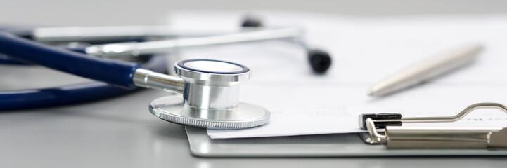 Stethoscope head lying on medical form on clipboard pad