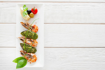 Plate with prepared seafood on white wooden background, copy space. Vertical position of dish with stuffed mussel and grilled shrimp, menu photo, free space for text