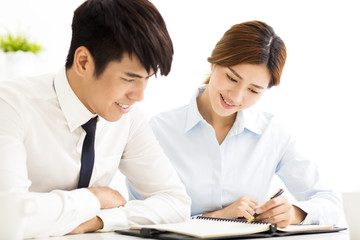 business man and woman discussing doucment in office