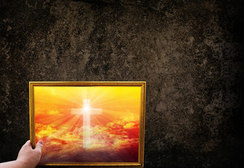 Hand hold picture frame of crucifix or cross on golden sky  on darkness grunge wall
