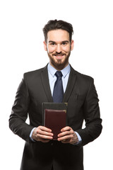 Young handsome man in black suit and business diary isolated on
