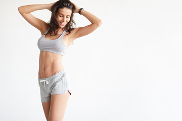 Attractive young adult in sportswear posing on white background.