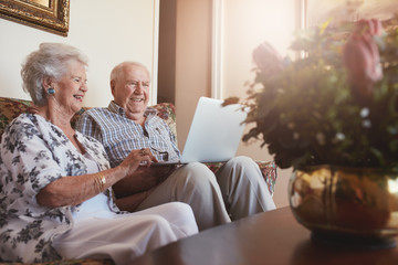Smiling senior couple using laptop at home