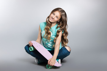 Girl posing with skateboard sitting in the studio. Joy, smile, positive emotions