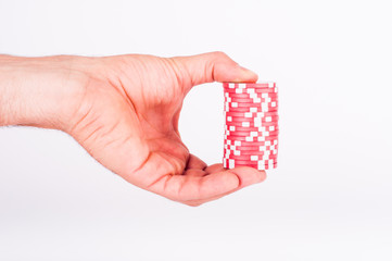 Red casino chips on human hands isolated on white