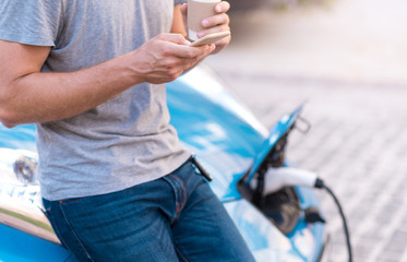 Man using smartphone while charging car