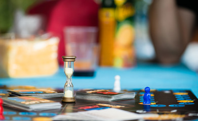 board game with an hourglass, chips and cards