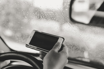 Car driver using smart phone, closeup on hand, mockup screen background