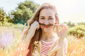 smiling teenage girl playing with her long hair as mustache
