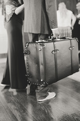 Black and white closeup on hand of elegant couple standing at reception holding suitcase. Walking hugging couple