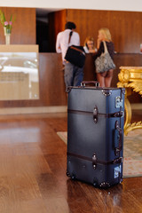 Retro style suitcase trunk ready for travel, background with defocused couple at the reception desk
