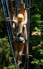 Adventure climbing high wire park - girl on course in mountain helmet and safety equipment