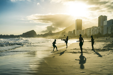 Football altinho silhouettes playing on the shore of Copacabana Beach at sunset in Rio de Janeiro, Brazil